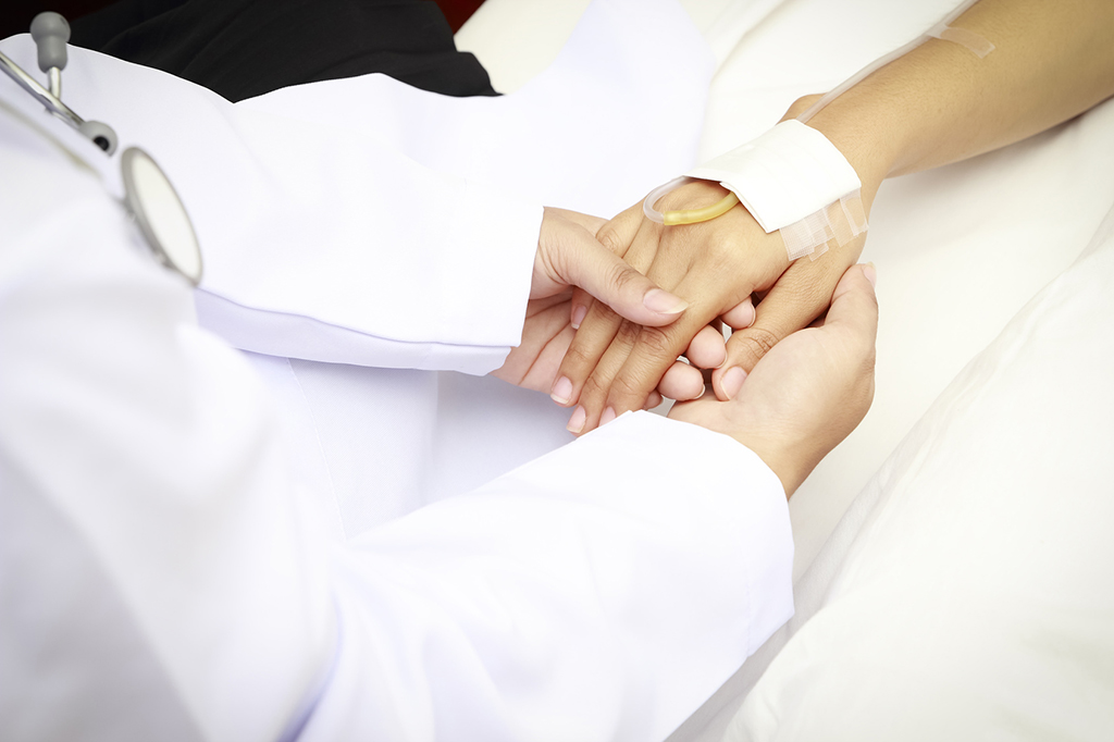 doctor holing patient's hands and comforting her